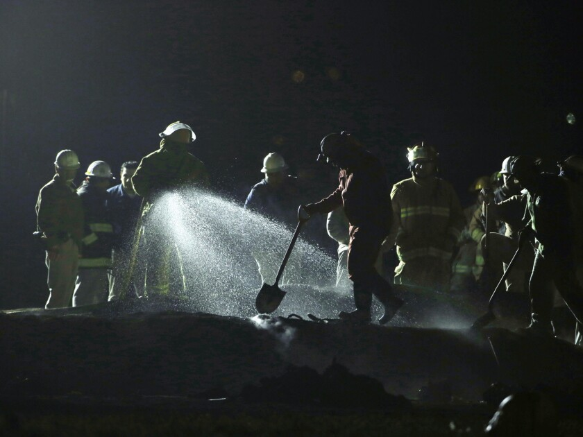 A crew from the state oil company Pemex works the burn area Saturday after the pipeline explosion in Tlahuelilpan, Mexico.