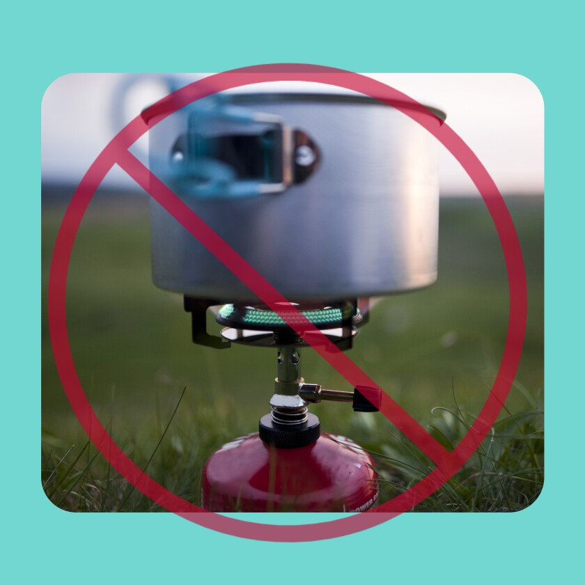 A camping stove with a red warning sign superimposed on it.