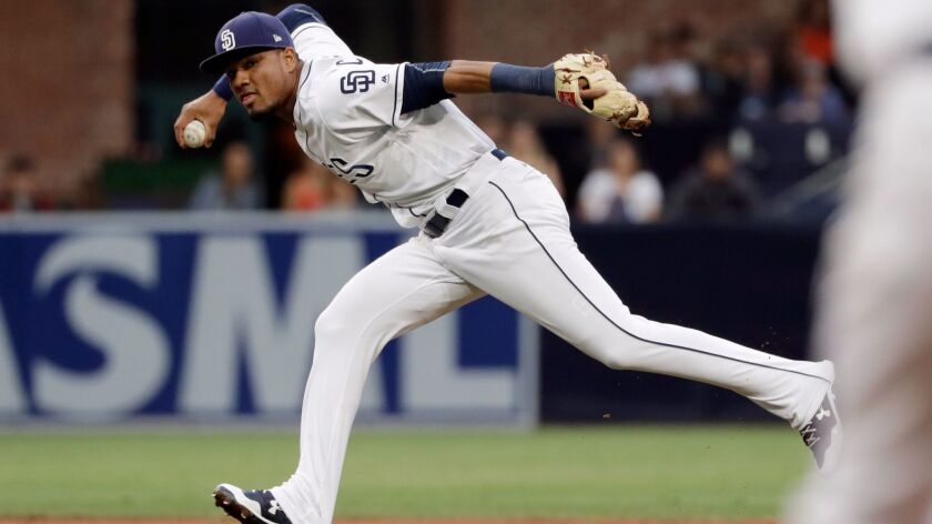 San Diego Padres shortstop Allen Cordoba looks to throw to first as Atlanta Braves' Johan Camargo ar