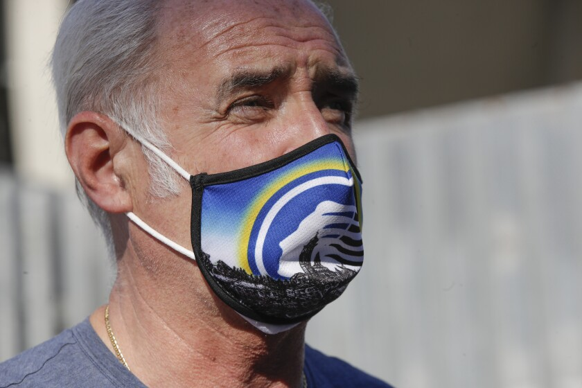 A supporter of Atalanta soccer team wears a face mask in the team's colors, prior to the Serie A soccer match between Atalanta and Sassuolo at the Gewiss Stadium in Bergamo, Italy, Sunday, June 21, 2020. Atalanta is playing its first match in Bergamo since easing of lockdown measures, in the area that has been the epicenter of the hardest-hit province of Italy's hardest-hit region, Lombardy, the site of hundreds of COVID-19 deaths. (AP Photo/Luca Bruno)