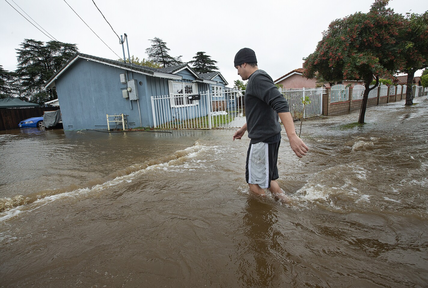 MISSION HILLS, CA-DECEMBER 4, 2019: Mission Hills resident Alberto Rodriguez, 32, walks through knee deep water on a flooded street outside of his home, at left, on Woodman Ave. The cause of the flood was a rupture from a 72 inch steel riveted trunk line that was installed back in 1914. (Mel Melcon/Los Angeles Times)