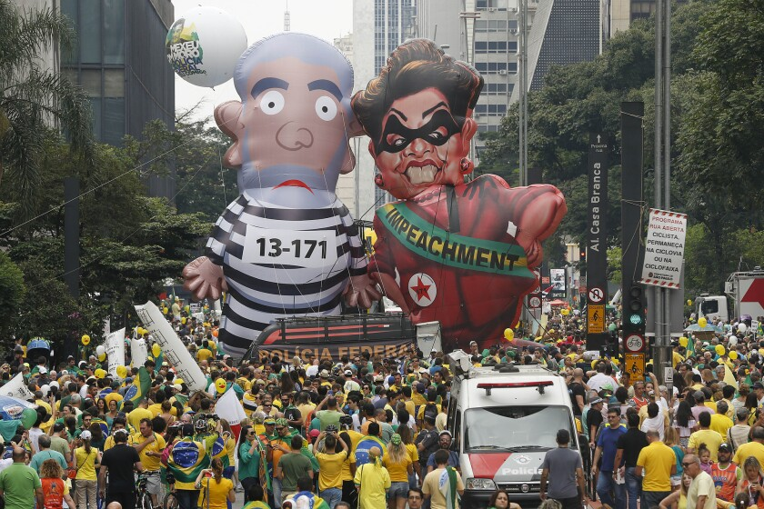 Brazilian demonstrators parade inflatable dolls depicting former President Luiz Inacio Lula da Silva as an inmate and current President Dilma Rousseff as a thief in Sao Paulo on Sunday.
