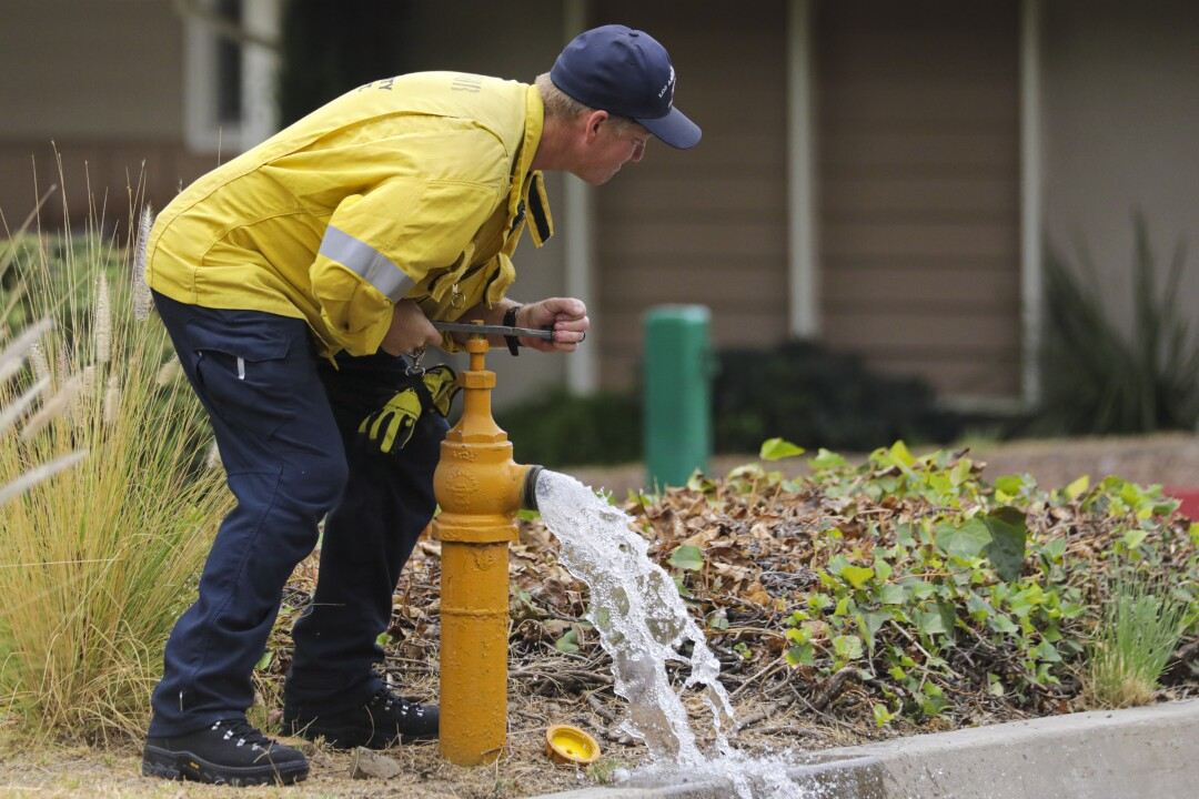 A firefighter shuts off a fire hydrant