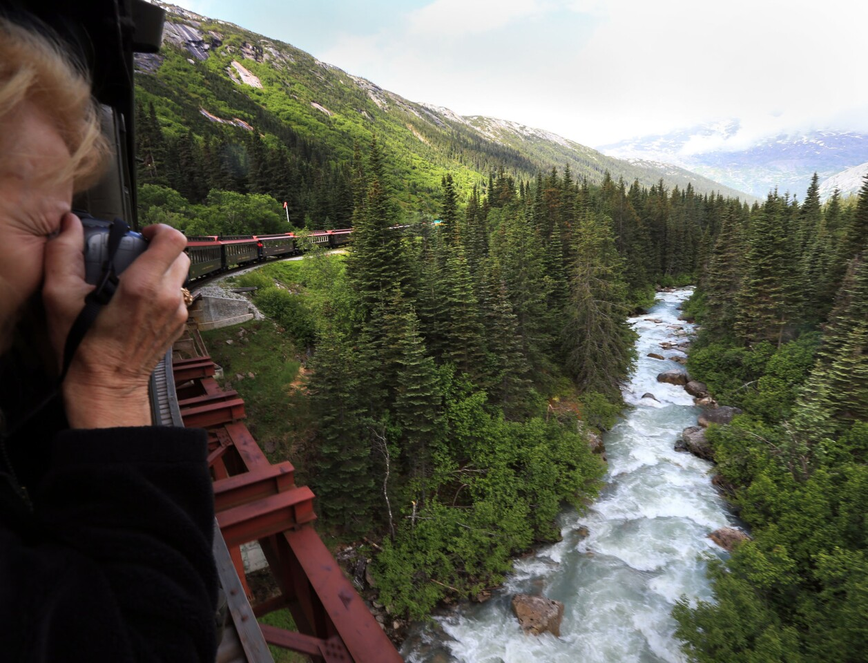 A passenger records a river scene from the train that travels from Skagway, Alaska into Canada.