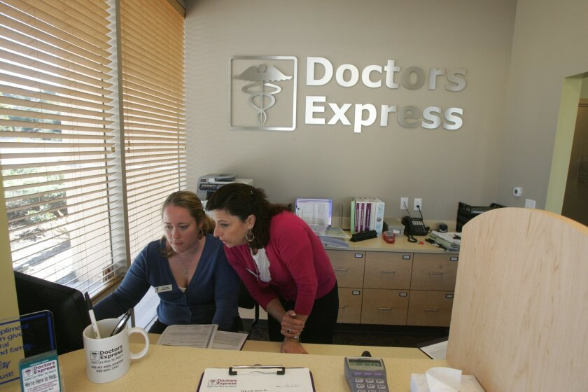 Doctors Express franchise owner Kari Knowles, left, and administrative director Kim Lewis work at the reception desk of the urgent care center that opened Sunday in Oceanside.