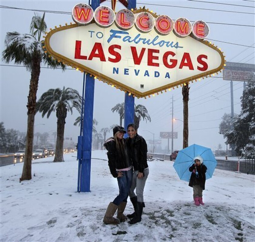 People line up to get photos in front of the famous Las Vegas sign in snow on the Las Vegas Strip Wednesday, Dec. 17, 2008.
