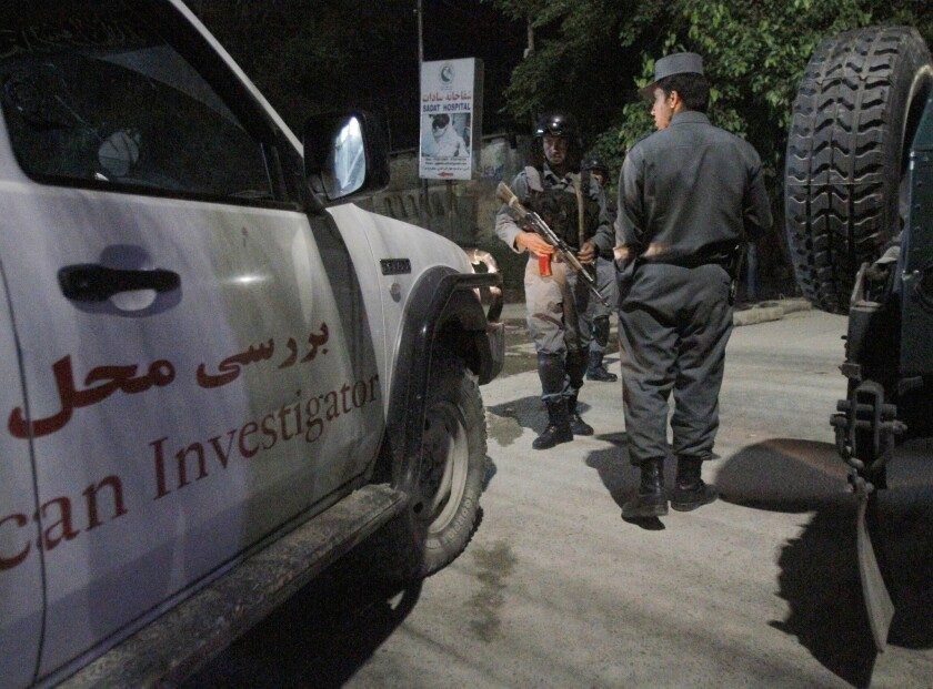 Afghan security forces inspect the site of an attack on a Kabul guesthouse on May 14.