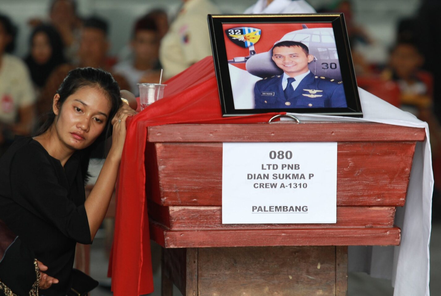 An Indonesian woman mourns beside the coffin of her relative, one of the victims of the crashed C-130 military airplane at a military airbase in Medan, North Sumatra, Indonesia on July 1, 2015.