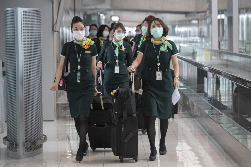 Flight crew wear protective masks as they arrive at the Suvarnabhumi Airport in Bangkok, Friday, July 3, 2020. As the country starts to ease its travel restrictions allowing foreign visitors in on a controlled basis, a laboratory at the airport will have the results of COVID-19 virus testing ready within 90 minutes for arriving travelers. (AP Photo/Sakchai Lalit)