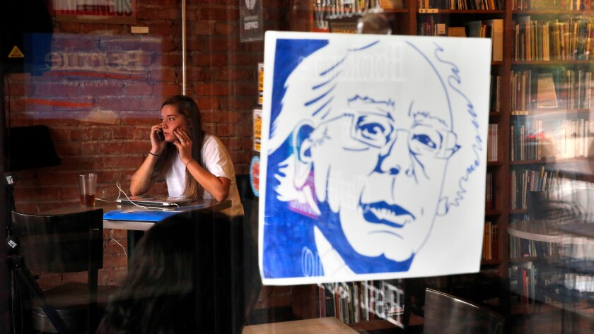 A young woman sits near a number of Bernie Sanders campaign posters that are still posted at the Innisfree Poetry Bookstore & Cafe, a popular hangout for students at the University of Colorado in Boulder.