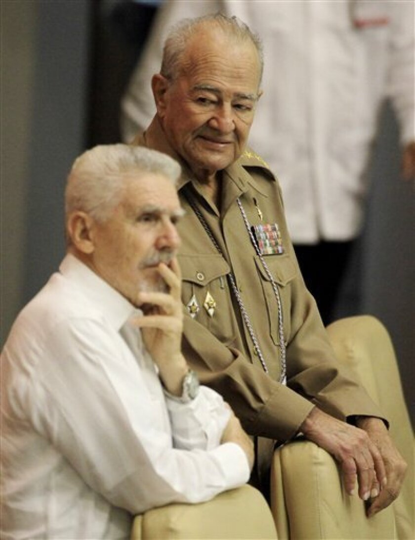 In this photo taken Monday, April 18, 2011, Cuba's Defense Minister Gen. Julio Casas Regueiro, right, and Cuba's Revolution commander Ramiro Valdes attend a 6th Congress of the Cuban Communist Party session in Havana, Cuba. Gen. Regueiro, who oversaw the Cuban military's lucrative economic enterprises for years before replacing Raul Castro as defense minister, died Saturday Sept. 3, 2011 of heart failure, Cuban state television reported. He was 75. (AP Photo/Javier Galeano)
