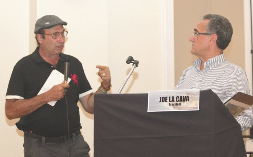 Keith Wahl speaks in favor of changing the name of the La Jolla Christmas Parade as LJCPA board Chair Joe LaCava looks on.