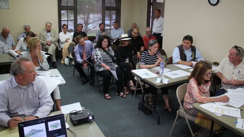 La Jolla Shores Permit Review Committee member Janie Emerson (striped shirt, center right) comments