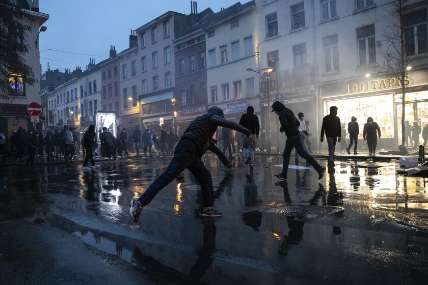 Protesters throw stones in Brussels at the end of a protest Wednesday over the death of a Black man in police custody.