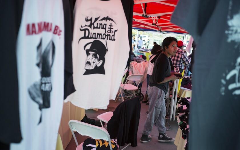 Street vendor Rufino Tzunun waits for customers at his T-shirt booth at the Westlake/MacArthur Park Metro Line station.