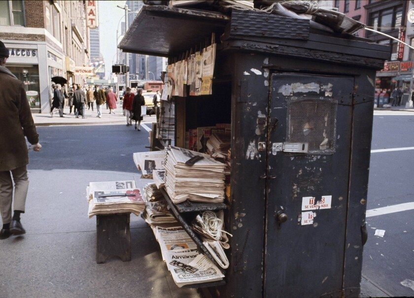 Bundles of newspapers are stacked up at a newsstand