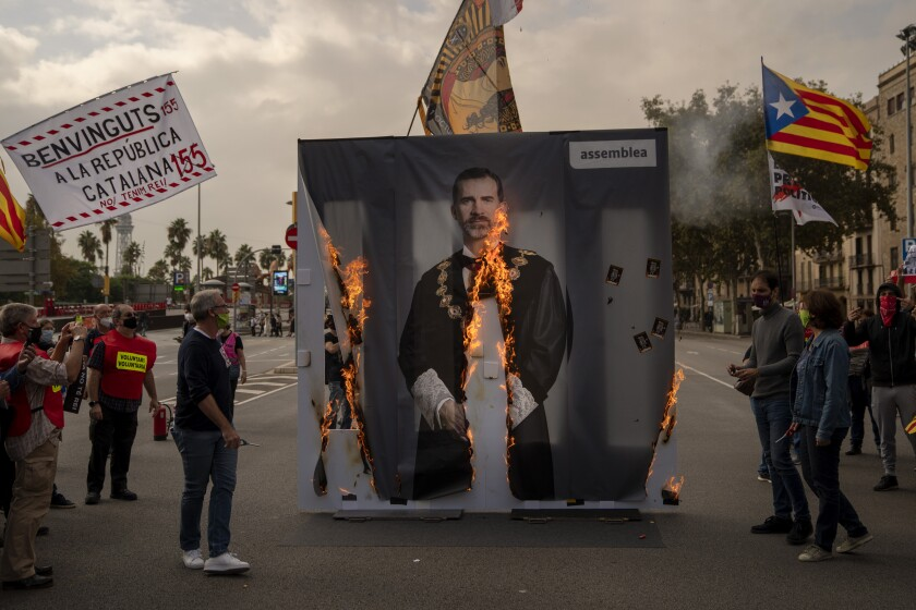 Activists of Catalonia's pro-independence grassroots group, ANC, burn a portrait of Spain's King Felipe VI during a demonstration in Barcelona on Friday, Oct. 9, 2020. Several thousand Catalan separatists are protesting the visit of Spanish King Felipe VI and Prime Minister Pedro Sánchez to Barcelona amid continued tensions between the restive region and national authorities. (AP Photo/Emilio Morenatti)