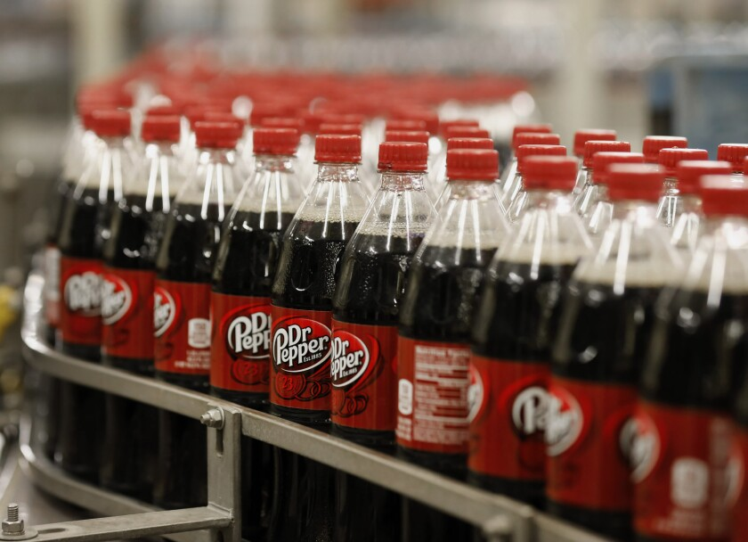 Bottles of Dr. Pepper soft drinks move along a production line at a bottling plant. A bill would require soda sold in California to have health warning labels.