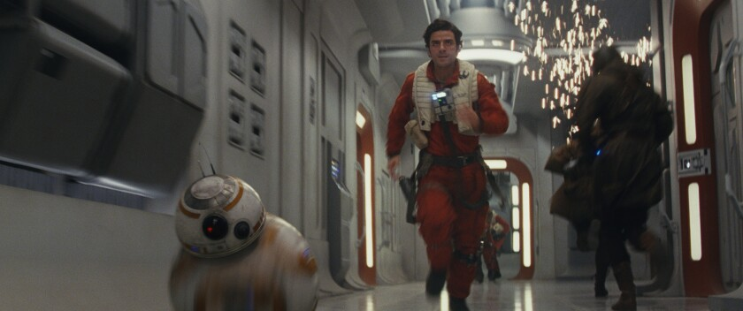 Oscar Isaac, playing Resistance pilot Poe Dameron, makes a run for it with BB-8.