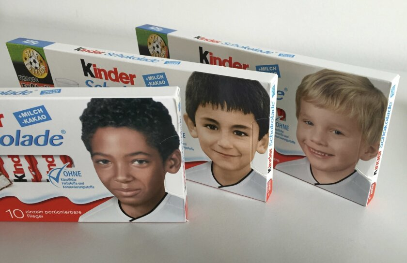 Packages of a popular chocolate bar with childhood pictures of German national soccer players, from left, Jerome Boateng, Ilkay Gundogan and Polish born Lukas Podolski are arranged on a table for a photograph in Berlin Wednesday, May 25, 2016. Candymaker Ferrero swapped the usual blond boy on its 'Kinder' bars ahead of this summer's European Championships for photos of German players as children and prompted online outrage among Germany's far right. Jerome Boateng, whose father is from Ghana, was born in Berlin and Ilkay Gundogan, whose parents are Turkish, was born in Gelsenkirchen. (AP Photo/Ferdinand Ostrop)