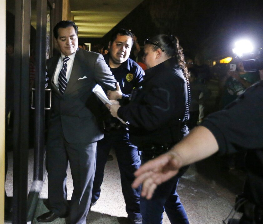 In this photo taken on Tuesday, Feb. 16, 2016, Crystal City Mayor Ricardo Lopez is taken away from city hall by police, in Crystal City, Texas,  after allegedly disrupting a City Council meeting while fighting a recall effort that began before his indictment this month in a public corruption invest