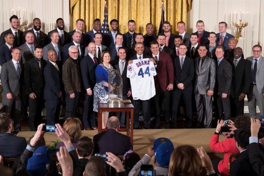 El presidente estadounidense, Barack Obama (c), posa junto al equipo de béisbol Cachorros de Chicago tras recibir una camiseta con su nombre durante un evento de bienvenida de los Cachorros de Chicago en la Casa Blanca para celebrar su victoria en la Serie Mundial de 2016, en Washington, Estados Unidos, hoy 16 de enero de 2017. EFE