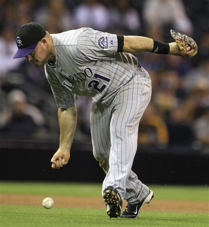 Colorado Rockies third baseman Ty Wigginton misses the bare hand pickup on a ball hit by San Diego Padres' Logan Forsythe in the seventh inning d of a baseball game Monday, June 6, 2011 in San Diego. Forsythe got a single on the first of two infield hits for the Padres in the inning. (AP Photo/Lenny Ignelzi)