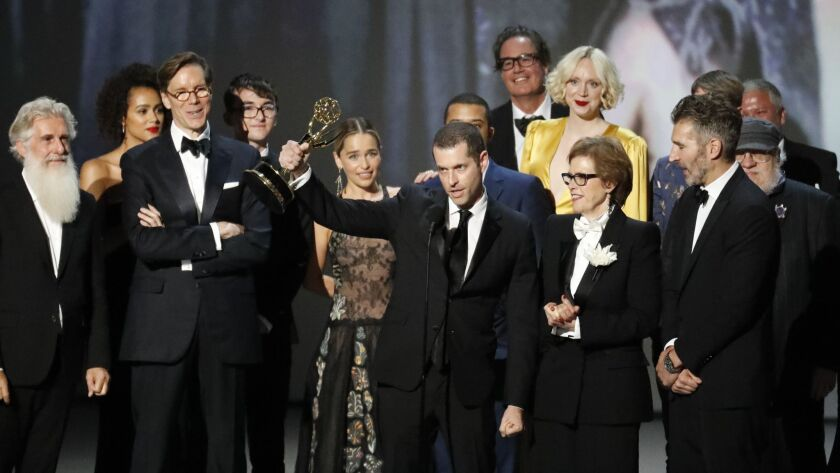 """""""Game of Thrones"""" producer and co-creator D.B. Weiss holds up the Emmy awarded to """"Game of Thrones"""" for outstanding drama series on Monday in Los Angeles. Co-executive producer Guymon Casady is standing in the back behind Weiss and actress Gwendoline Christie in the yellow gown."""
