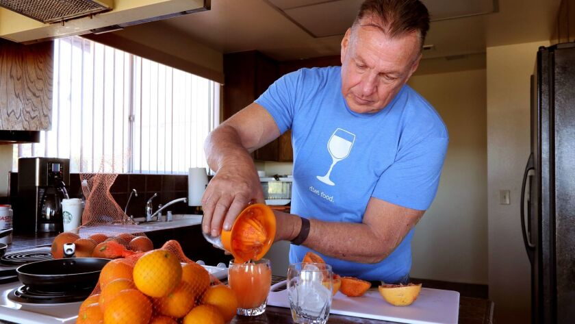Doug Siverly makes orange juice from oranges he just picked at his rural area home after a strenuous morning walk.