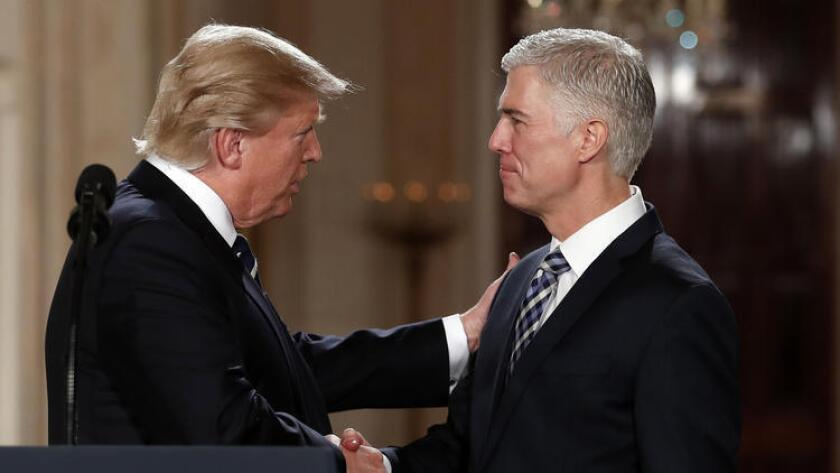 President Trump shakes the hand of his Supreme Court nominee, federal appeals court Judge Neil Gorsuch, on Tuesday night at the White House.