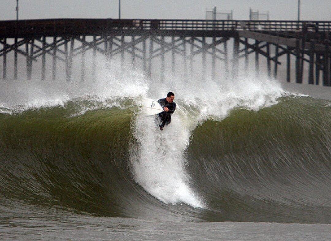 A surfer rides a wave at Seal Beach