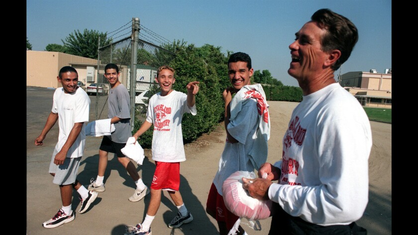 McFarland High cross-country coach Jim White shares a laugh with some team members in 1997, shortly after the team's portrait was taken for the school yearbook.