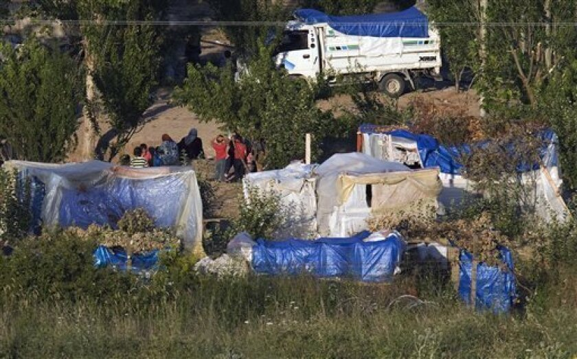 Syrians living in makeshift tents inside Syria near the Turkish border village of Guvecci are seen shortly before Turkey's Red Cresdent distribute free food alongside Turkey-Syria border near the Turkish village of Guvecci in Hatay province, Turkey, late Wednesday, June 22, 2011. (AP Photo/Burhan Ozbilici)