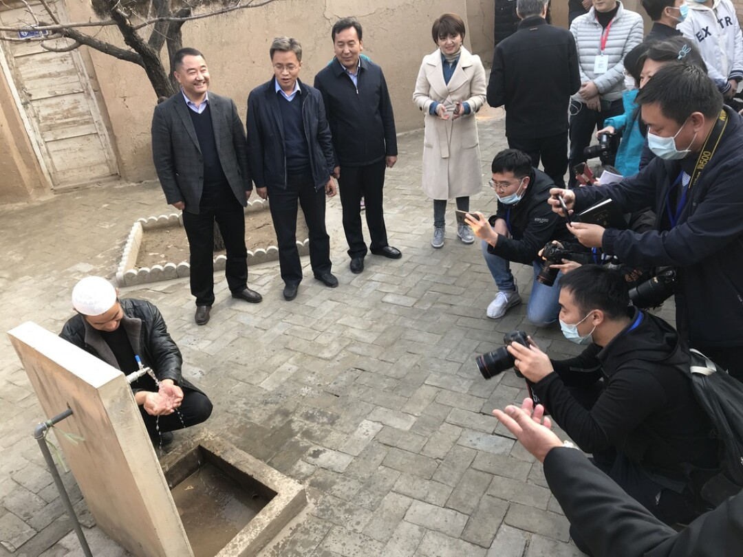 Inside a village museum honoring Xi Jinping's visit to Bulengou in 2013, a Dongxiang man washed his hands in running water.