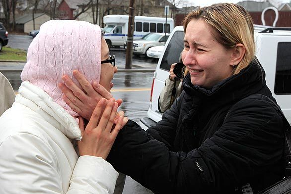 Survivor Zhanar Tokhtabayeva, 30, left, from Kazakhstan, embraces an unidentified woman in Binghamton, N.Y. A gunman opened fire on an immigration center earlier in the day, killing 13 before apparently committing suicide.