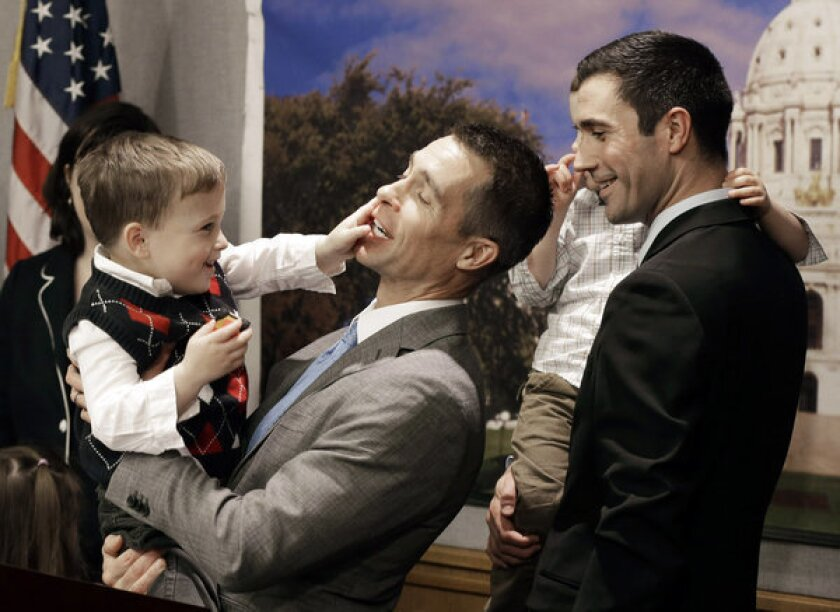 Dr. Paul Melchert, left, with his son, Emmett, as he attempts to address the media while his partner James Zimerman, right, holds twin, Gabriel, during a news conference in St. Paul, Minn., where lawmakers introduced a bill to legalize gay marriage in Minnesota. On Thursday the American Academy of Pediatrics, the most influential U.S. pediatricians' group, endorsed gay marriage, saying a stable relationship between parents regardless of sexual orientation contributes to a child's health and well-being.