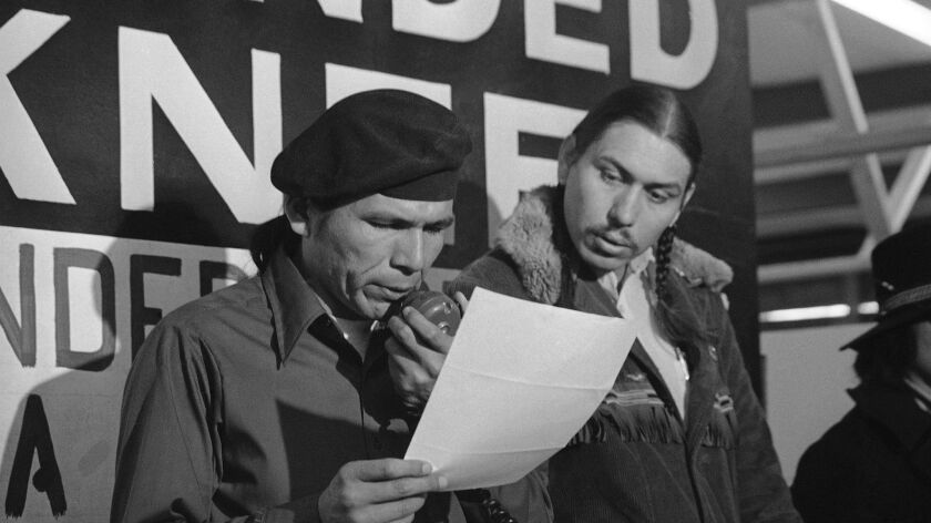 American Indian Movement leader Dennis Banks, left, reads an offer from the U.S. government seeking to end the Native American occupation of Wounded Knee. Looking on is AIM leader Carter Camp.