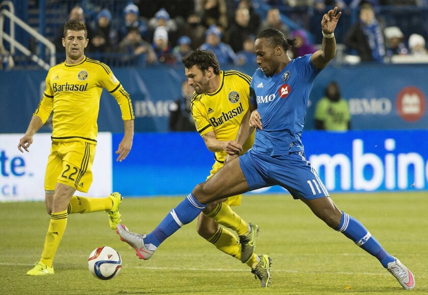 Montreal Impact's Didier Drogba, right, challenges Columbus Crew SC's Michael Parkhurst, center, as Crew's Gaston Sauro (22) looks on during the first half of an MLS soccer game in Montreal, Sunday, Nov. 1, 2015. (Graham Hughes/The Canadian Press via AP) MANDATORY CREDIT