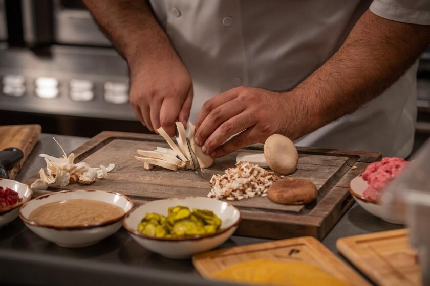 Chef Jose Mendoza chops Escondido-grown mushrooms for his Psycho-Deli Burger at the Lobby Bar & Grill at Pechanga Resort Casino in Temecula.
