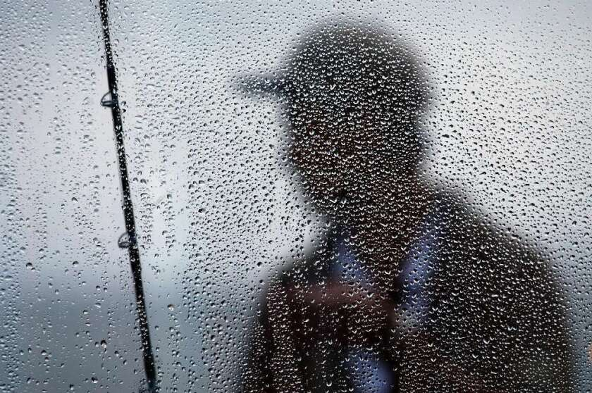 A fisherman is framed in the fog-soaked window of a restaurant on the Newport Beach pier. Urban sprawl is reducing fog in coastal Southern California.