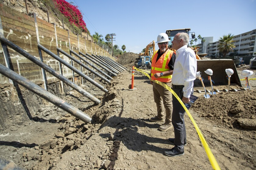 Don Fansler, left, of the East Los Angeles Community Union talks with Larry Frapwell, the architect overseeing the project, during a groundbreaking ceremony Monday for Orange Coast College's new Professional Mariner Training Center. The site is across West Coast Highway from the marine program's sailing and rowing base at Newport Harbor.