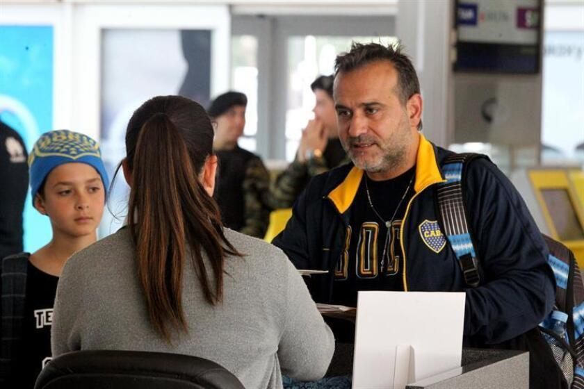 Aficionados del Boca Juniors se registran para abordar un vuelo con rumbo a Madrid, hoy, en el Aeropuerto Internacional de Ezeiza, en Buenos Aires (Argentina). EFE