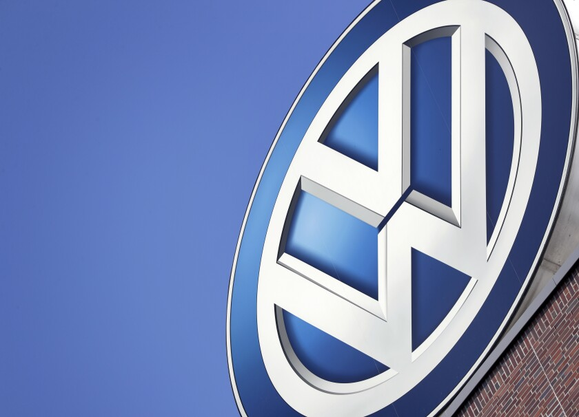 FILE - In this Wednesday, Aug. 1, 2018 file photo, the logo of Volkswagen is seen on top of a company building in Wolfsburg, Germany. German prosecutors say they have charged Volkswagen chief executive Herbert Diess and chairman Hans Dieter Poetsch, along with former CEO Martin Winterkorn, with market manipulation in connection with the diesel emissions scandal that erupted in 2015. (AP Photo/Michael Sohn, file)