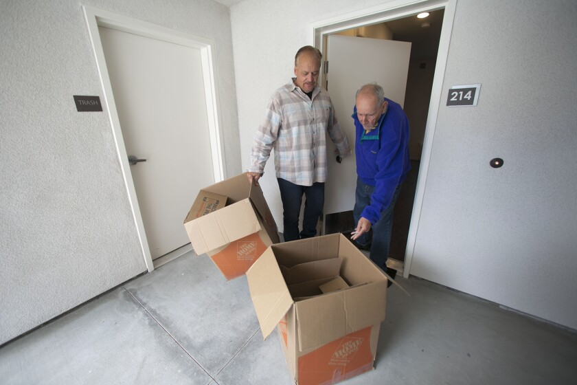 Alpha Project CEO Bob McElroy helps veteran Steven Ferguson, 70, move empty boxes after Ferguson moved in at the Alpha Lofts apartments in Normal Heights.