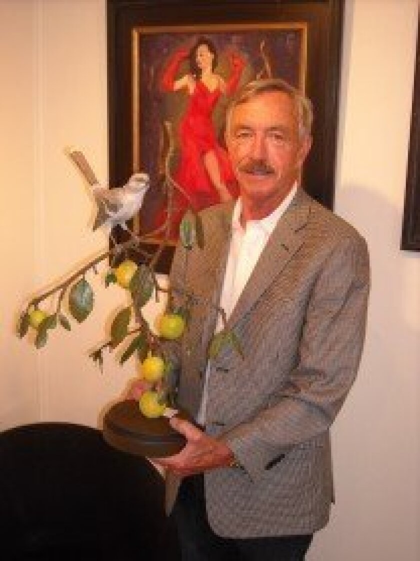Dale Steffen holding sculpture of northern mockingbird in lemon tree. Photos/Will Bowen