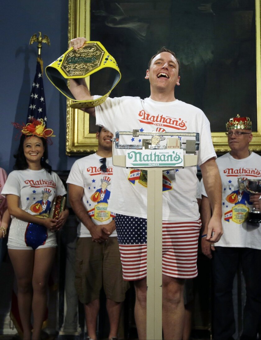 Seven-time hot dog eating champion, Joey Chestnut, poses while weighing in during a news conference to promote the upcoming Nathan's Famous Fourth of July International Hot-Dog Eating Contest tomorrow Thursday, July 3, 2014, at City Hall in New York. (AP Photo/Frank Franklin II)