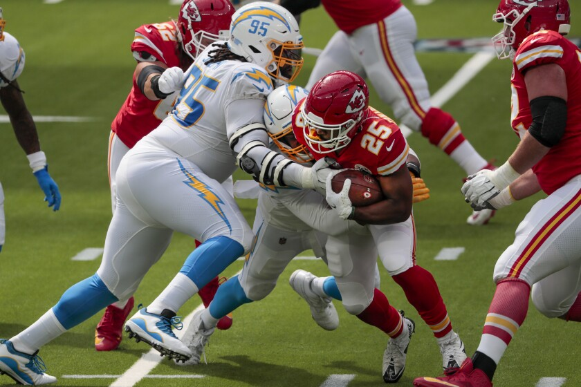 Chiefs running back Clyde Edwards-Helaire is tackled by Chargers defensive tackle Linval Joseph and Isaac Rochell.