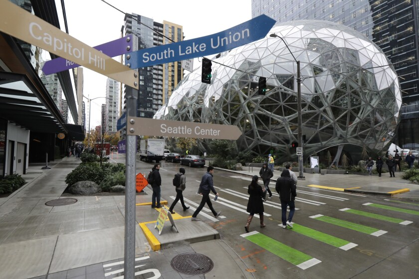 In this Nov. 9, 2018 photo, pedestrians walk near the Amazon Spheres in downtown Seattle as a sign p