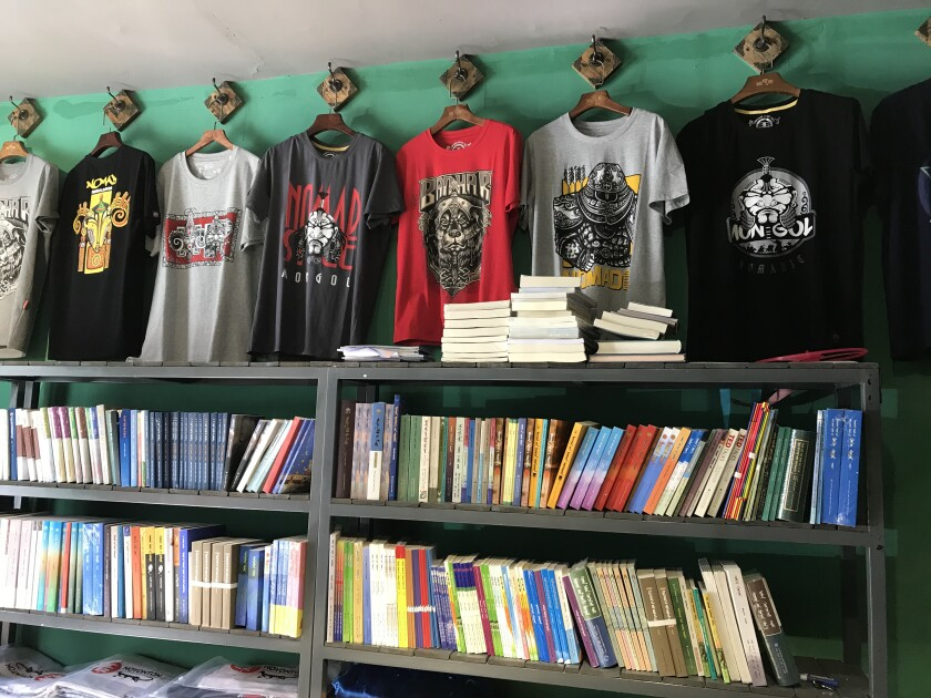 A shop sells T-shirts with popular Mongolian symbols and band names, and Mongolian-language books.