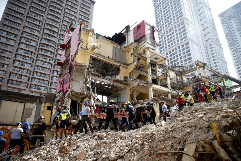 """Rescuers search for victims after a budget hotel which is undergoing demolition, collapsed Monday, Sept. 23, 2019, in Manila, Philippines. Rescue efforts are still ongoing to free another victim after one of the workers was retrieve after almost six hours following the incident, according to Manila Mayor Francisco """"Isko Moreno"""" Domagoso. (AP Photo/Bullit Marquez)"""